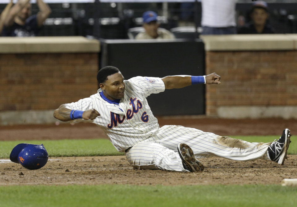 Photo - New York Mets' Marlon Byrd reacts after sliding home safe to tie the game during the ninth inning of the baseball game against the Arizona Diamondbacks at Citi Field, Monday, July 1, 2013, in New York. (AP Photo/Seth Wenig)
