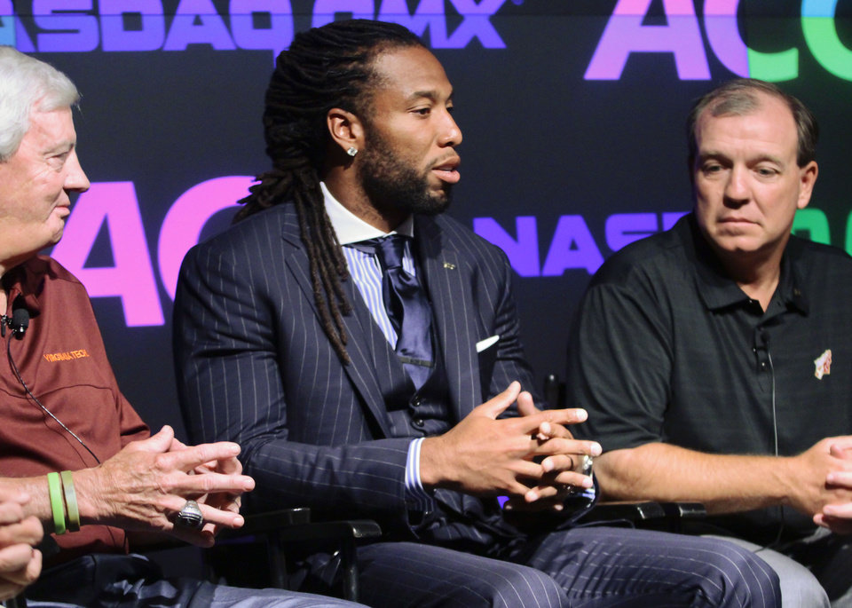 Photo - Virginia Tech men's football coach Frank Beamer, left, and Florida State men's football coach Jimbo Fisher, right, listen to Larry Fitzgerald, former Pitt football All-American and Pro Bowl wide receiver, center, during a press conference on Monday, July 1, 2013 in New York.  ACC officials and coaches visited the NASDAQ Market Site in Times Square to officially announce the addition of its three new members in Notre Dame, Pitt and Syracuse.  (AP Photo/Bethan McKernan)