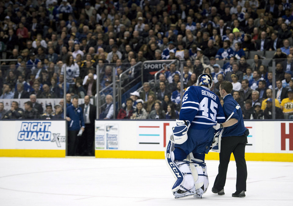 Photo - Toronto Maple Leafs goaltender Jonathan Bernier is helped off the ice after being injured during the third period of an NHL hockey game against the Boston Bruins in Toronto on Thursday, April 3, 2014. (AP Photo/The Canadian Press, Frank Gunn)