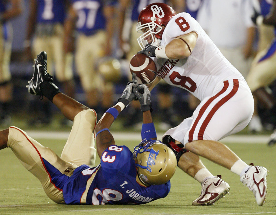 Photo - Oklahoma's Ryan Reynolds (8) gets the ball from Tulsa's Trae Johnson (83) for an interception during the first half of the college football game between the University of Oklahoma Sooners (OU) and the University of Tulsa Golden Hurricanes (TU) at H.A. Chapman Stadium on Friday, Sept. 21, 2007, in Tulsa, Okla.   By STEVE SISNEY, The Oklahoman  ORG XMIT: KOD