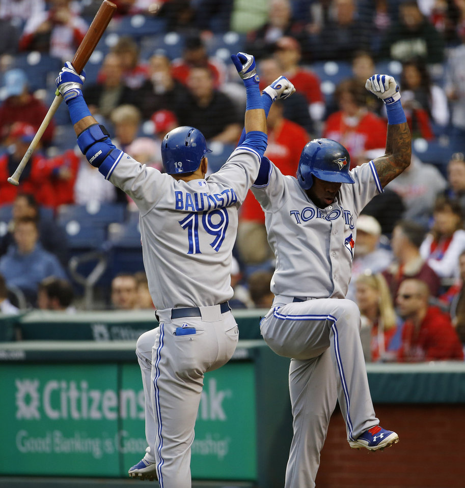 Photo - Toronto Blue Jays' Jose Reyes, right, and Jose Bautista celebrate after Reyes' home run during the first inning of an interleague baseball game against the Philadelphia Phillies, Monday, May 5, 2014, in Philadelphia. (AP Photo/Matt Slocum)