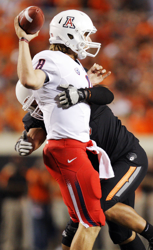 Photo - Oklahoma State's Jamie Blatnick pressures Arizona's Nick Foles in the second quarter of their game Thursday in Stillwater. PHOTO BY NATE BILLINGS, The Oklahoman