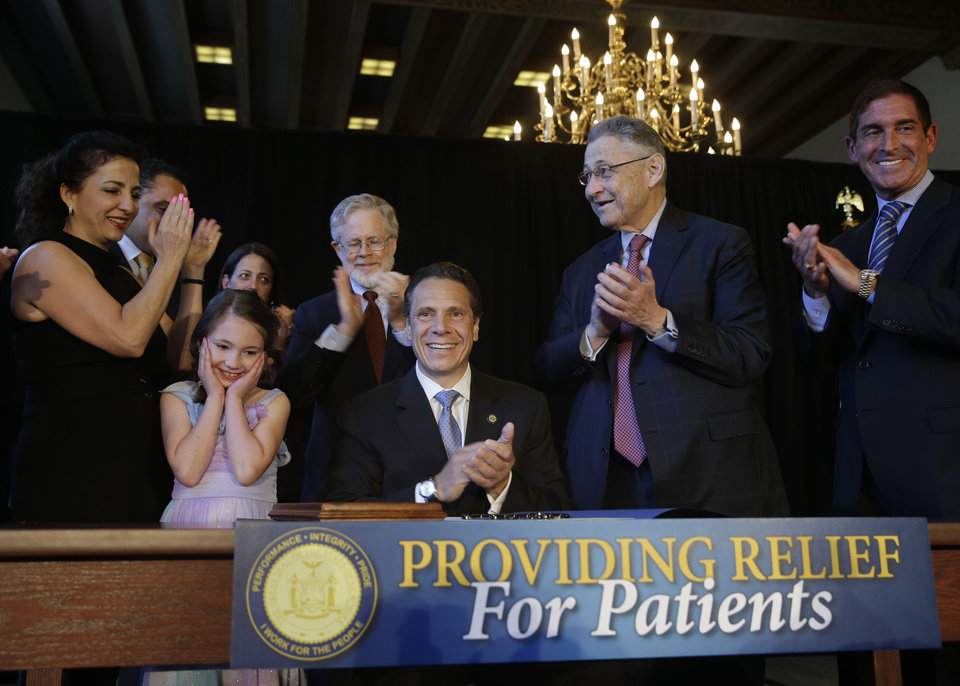 Photo - Politicians and supporters celebrate after New York Governor Andrew Cuomo, center, signed a ceremonial bill to establish a medical marijuana program in New York, Monday, July 7, 2014.  New York has become the 23rd state in the U.S. to authorize medical marijuana,  though the state's program is one of the nation's most restrictive.  Cuomo signed the measure into law on Saturday and held the formal signing ceremony on Monday to highlight the new law.  When the program gets up and running in about 18 months, patients with diseases including AIDS, cancer and epilepsy will be able to obtain non-smokeable versions of the drug. Instead, the drug must be ingested or administered through a vaporizer or oil base. (AP Photo/Seth Wenig)