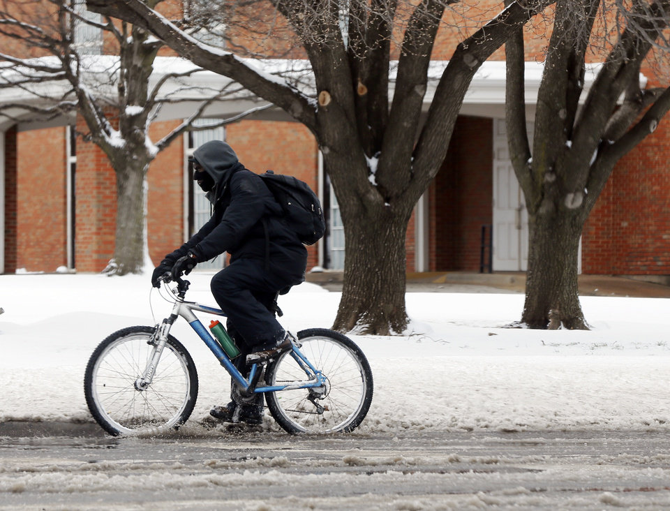 Photo - A cyclist rides south on May Ave. near NW 50 after a snow storm in Oklahoma City, Wednesday, Feb. 5, 2020. [Nate Billings/The Oklahoman]