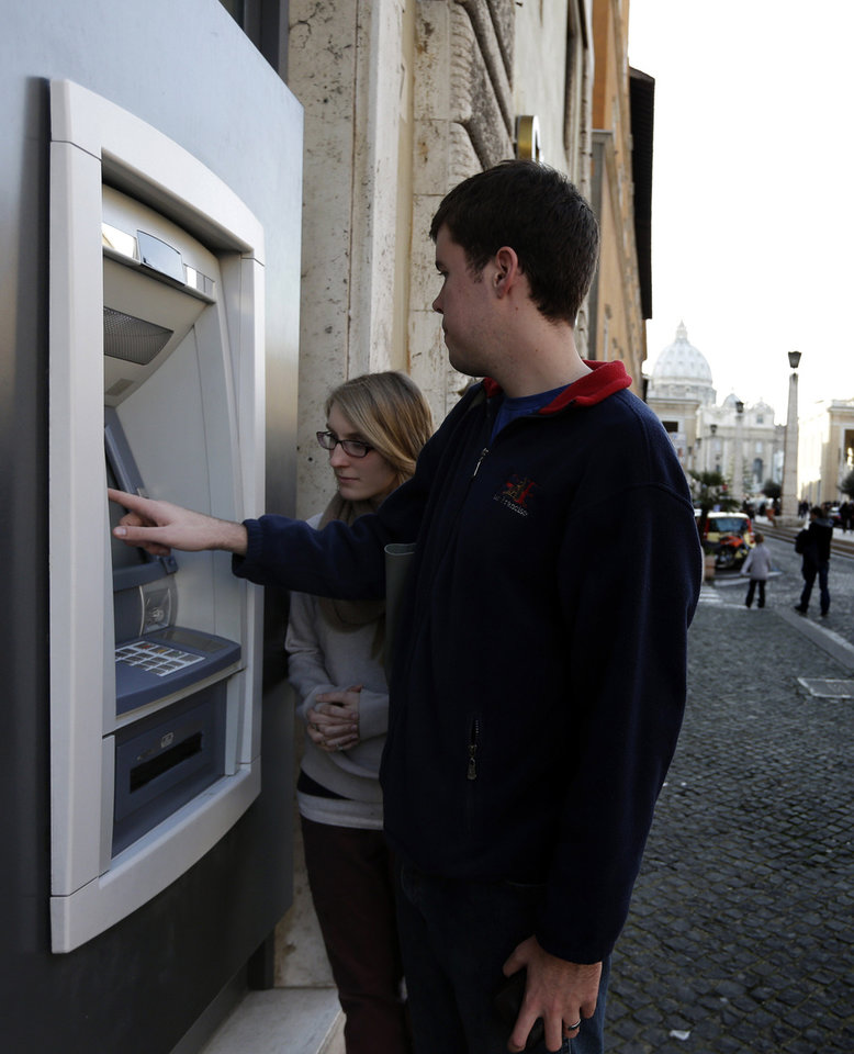 Photo - Ben Kiniry, of Texas, gets cash from an ATM machine along Via della Conciliazione, the main road leading to St. Peter's Basilica at the Vatican, Thursday, Jan. 3, 2013. It's