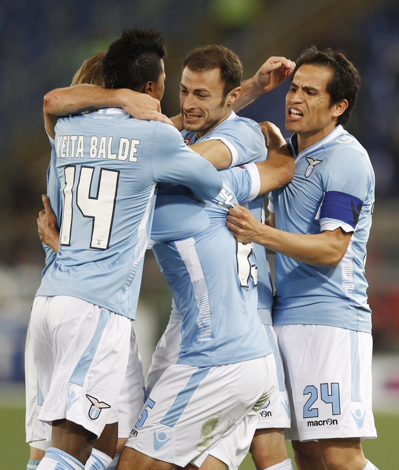 Photo - Lazio midfielder Alvaro Gonzalez of Uruguay, center, is celebrated by his teammates after he scored during a Serie A soccer match between Lazio and AC Milan, at Rome's Olympic Stadium, Sunday, March 23, 2014. (AP Photo/Andrew Medichini)