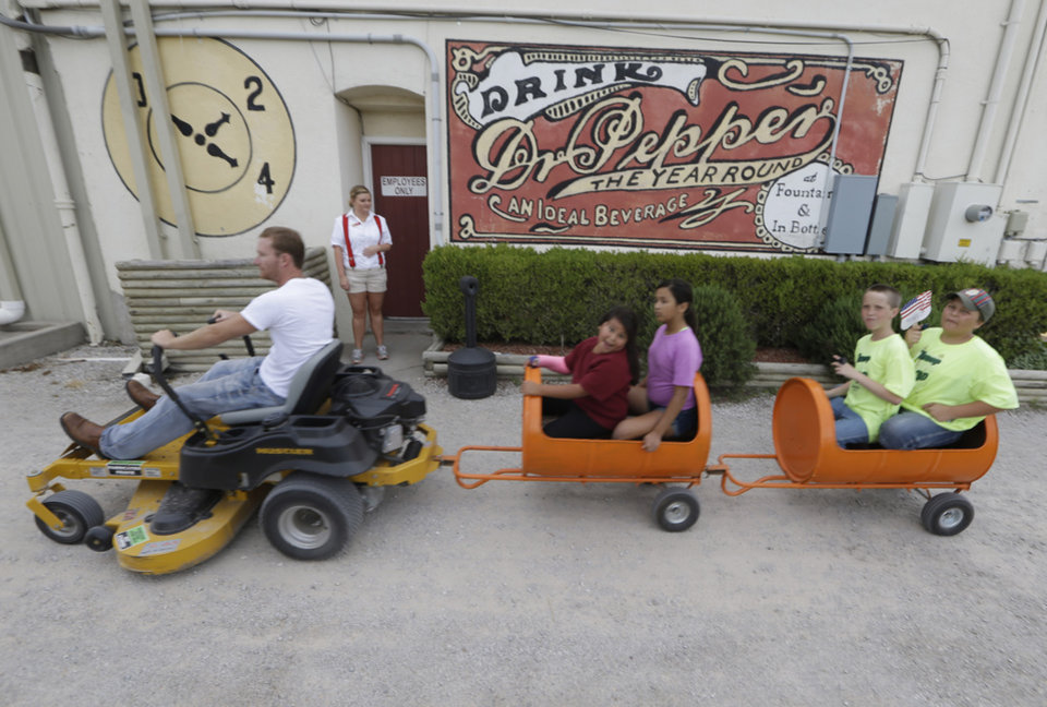 Photo - In this June 14, 2014 photo, kids get a lawnmower train ride past the the Dublin Bottling Co in Dublin, Texas.More than two years after Dr Pepper cut ties with the local bottler over a licensing dispute, the town is trying to stabilize its economy by promoting its lesser-known claims to fame, from a festival highlighting its debatable Irish roots, to Dublin's bygone rodeo glories, to its location within the county Dairy Capital of Texas. (AP Photo/LM Otero)