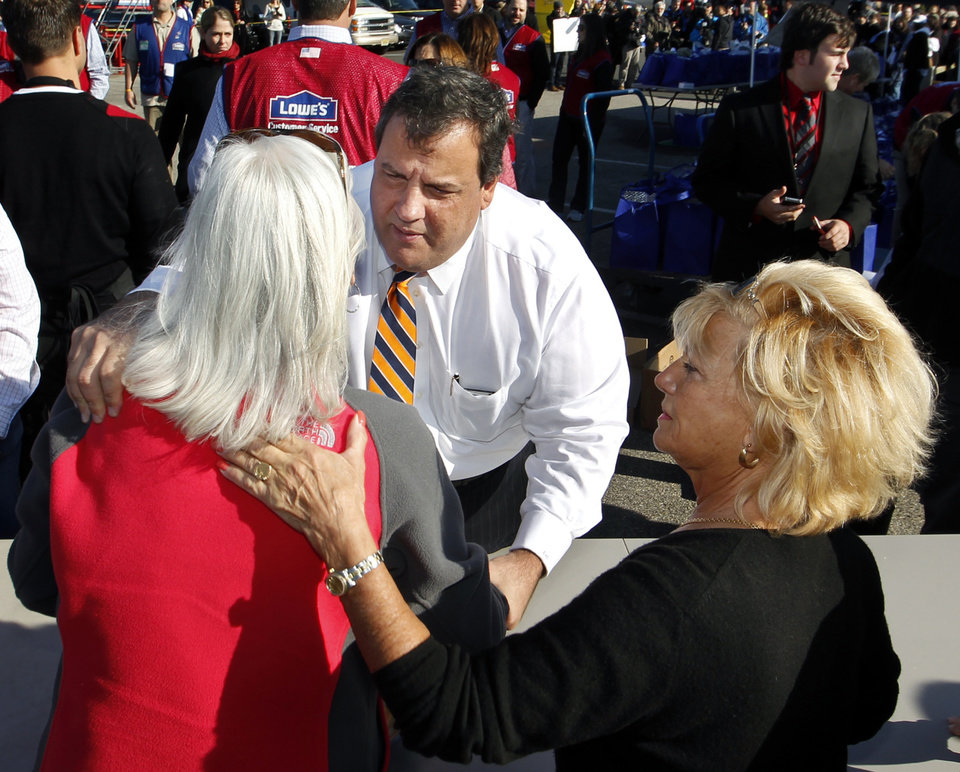 Chick Sorbello, right, of Lavallette, N.J., consoles Elizabeth Docimo of Brick, as she talks about damage to the shore with Gov. Chris Christie in Toms River, N.J., Wednesday, Nov. 21, 2012, as Christie, his wife Mary Pat Christie and other volunteers handed out prepared Thanksgiving dinners to the needy near the shore area devasted by Superstorm Sandy. (AP Photo/Mel Evans)