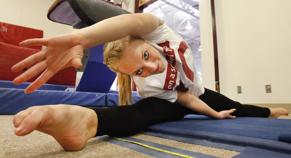 Kayla Nowak stretches during OU gymnastics practice, Monday, April 1, 2013. Nowak was doing a move on the uneven bars that she's done thousands of times. But last December, her heels caught on the bar like they never had before and it changed her life. She nearly severed her spinal cord. Photo By David McDaniel/The Oklahoman <strong>David McDaniel - The Oklahoman</strong>