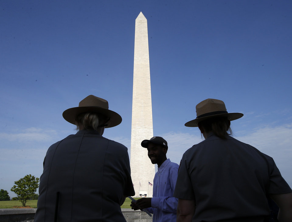 Photo - Park Service employees stand watch as visitor Roman Tanner, center, walks away with his Washington Monument ticket, which are distributed at on a first-come basis at the Washington Monument in Washington, Monday, May 12, 2014, ahead of a ceremony to celebrate its re-opening. The monument, which sustained damage from an earthquake in August 2011, is reopening to the public today. (AP Photo)