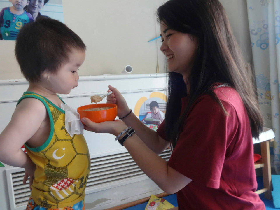 "Photo -  Abigale ""Abbey"" White, a Deer Creek High School student, feeds an orphan known as Jia Jia during her recent visit to the China Care Home, an orphanage in Beijing. Photo provided"