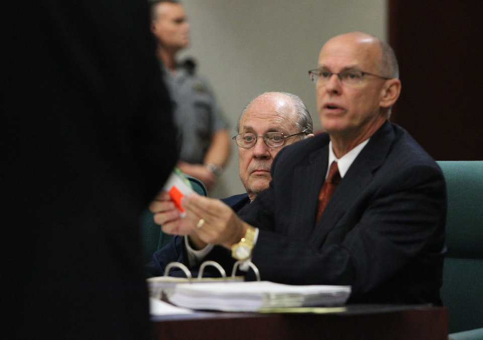 Photo - Former Tampa Police captain Curtis Reeves, Jr., left, sits beside his defense attorney Richard Escobar, right, during his bond reduction hearing before Circuit Judge Pat Siracusa at the Robert D. Sumner Judicial Center in Dade City Friday, Feb. 7, 2014. Reeves is suspected of fatally shooting Chad Oulson, 43, and wounding his wife, Nicole, 33, during an argument Jan. 13 over texting at the Cobb Grove 16 theater in Wesley Chapel, Fla.  (AP Photo/Pool Tampa Bay Times, Brendan Fitterer, Pool)