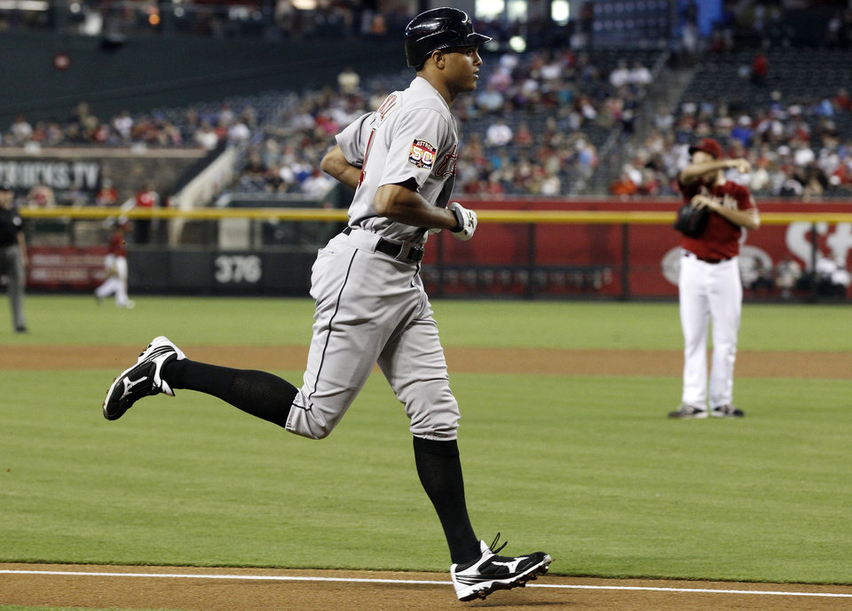 Photo -   Houston Astros' Justin Maxwell, left, rounds the bases after hitting a home run against Arizona Diamondbacks' Josh Collmenter, right, in the second during a baseball game on Sunday, July 22, 2012, in Phoenix.(AP Photo/Ross D. Franklin)