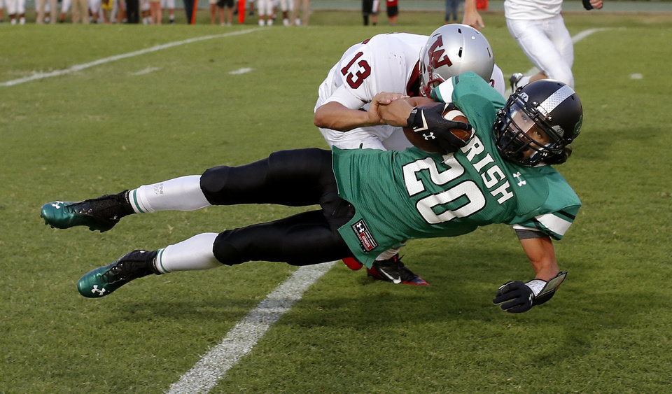 Photo - Braden Roy of Bishop McGuinness is brought down by Weatherford's Garrett Gaunt on a punt return during their high school football game in Oklahoma City, Friday, Sept. 20, 2013. A penalty for an illegal block in the back was called on the play. Photo by Bryan Terry, The Oklahoman