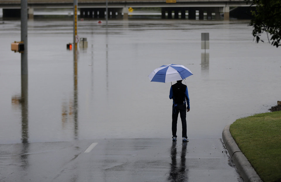 Photo - A man surveys floodwaters caused by heavy rains, Saturday, May 25, 2013, in San Antonio. (AP Photo/Eric Gay)