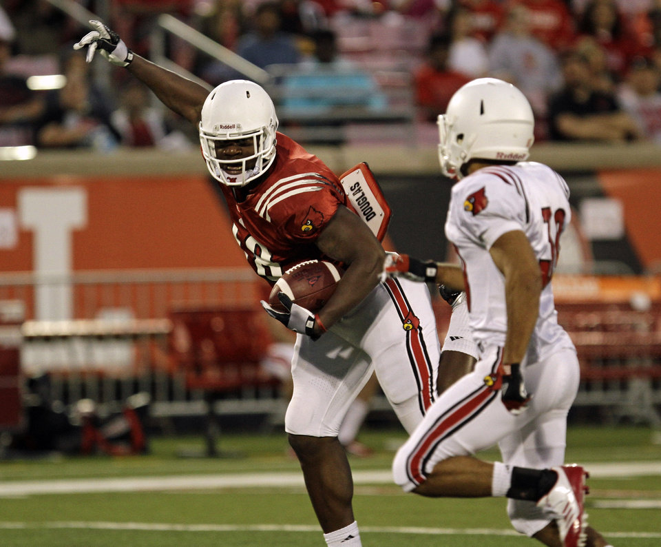 Photo - Louisville's Gerald Christian, left, makes a catch off balance in front of defender Jordan Streeter, right, in their NCAA college spring football game in Louisville, Ky., Friday, April 11, 2014.  (AP Photo/Garry Jones)