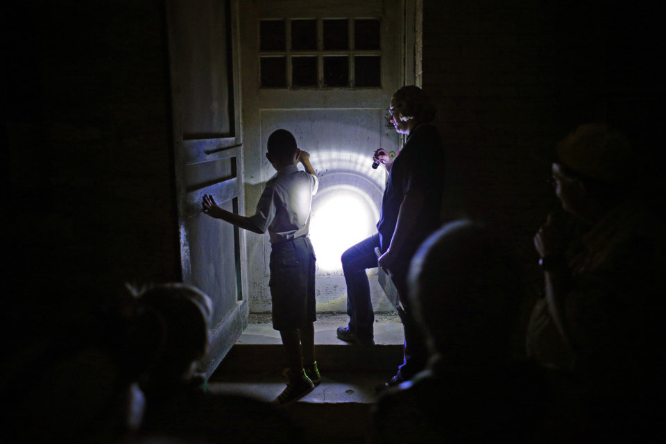 Photo -  Elias Padilla, from Boy Scout Troop 20, knocks on a door beside tour guide Rebecca Terrel as they try to get a respond from spirits during a guided ghost tour by lantern light around Fort Reno in El Reno on Saturday, Sept. 21, 2013. Photo by Bryan Terry, The Oklahoman