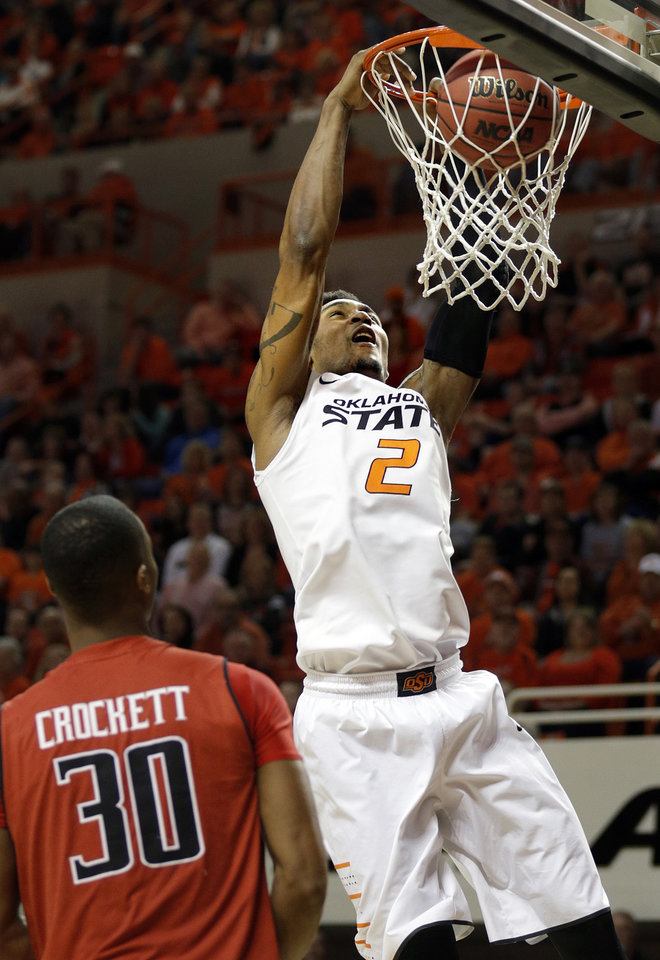 Photo - Oklahoma State's Le'Bryan Nash (2) dunks in front of Jaye Crockett (30) during the men's college basketball game between Oklahoma State and Texas Tech at Gallagher-Iba Arena in Stillwater, Okla., Saturday, Feb. 22, 2014. OSU won 84-62. 