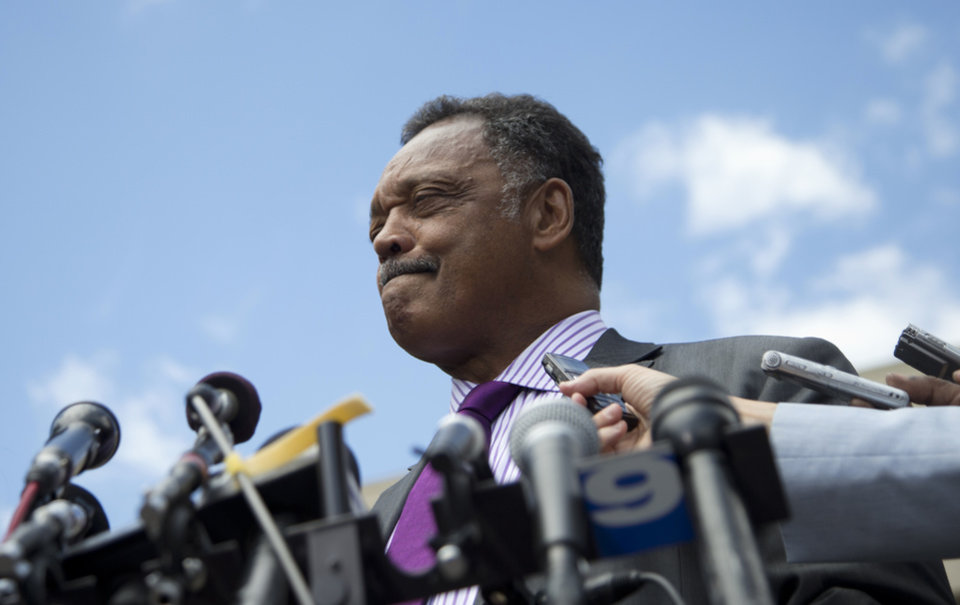 Photo - Rev. Jesse Jackson pauses as he he speaks to media outside federal court in Washington, Wednesday, Aug. 14, 2013, after his  son, former Illinois Rep. Jesse Jackson Jr., was sentenced to two and a half years in prison after pleading guilty to scheming to spend $750,000 in campaign funds on TV's, restaurant dinners, an expensive watch and other costly personal items. Jackson Jr.'s wife Sandra Jackson received a sentence of one year. (AP Photo/Carolyn Kaster)