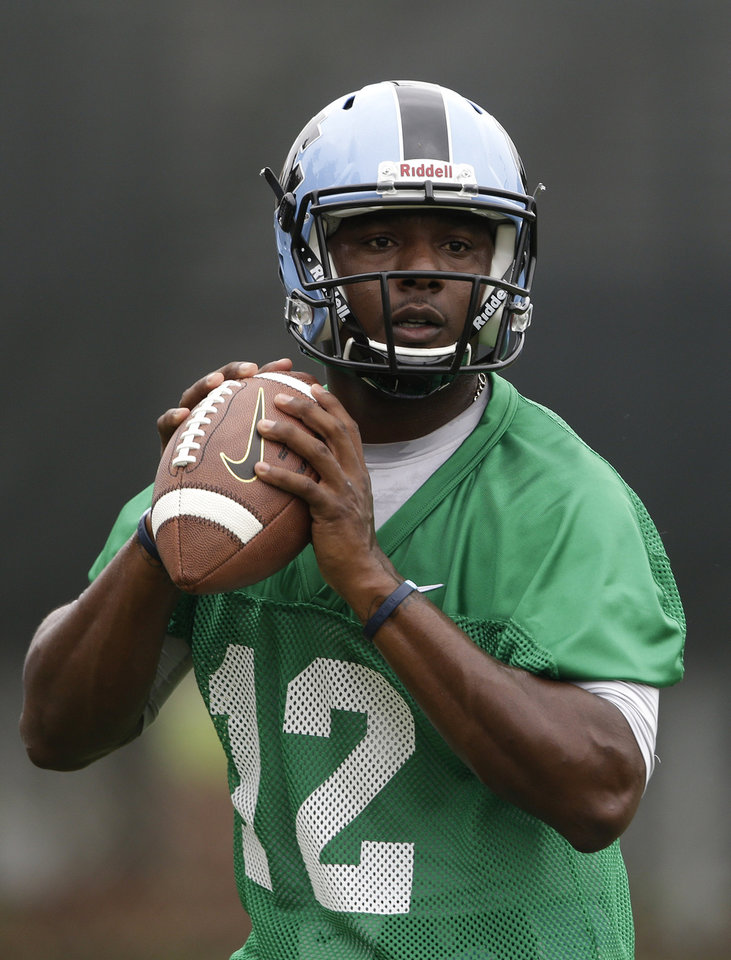 Photo - In this photo taken Friday, Aug. 1, 2014,  North Carolina quarterback Marquise Williams (12) participates in a passing drill during an NCAA football practice in Chapel Hill, N.C. (AP Photo/Gerry Broome)