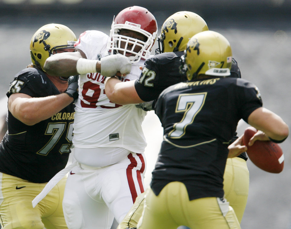 Photo - Daniel Sanders, left, and Devin Head of Colorado keep Gerald McCoy of OU away from Cody Hawkins during the first half of the college football game between the University of Oklahoma Sooners (OU) and the University of Colorado Buffaloes (CU) at Folsom Field on Saturday, Sept. 28, 2007, in Boulder, Co.  By Bryan Terry, The Oklahoman