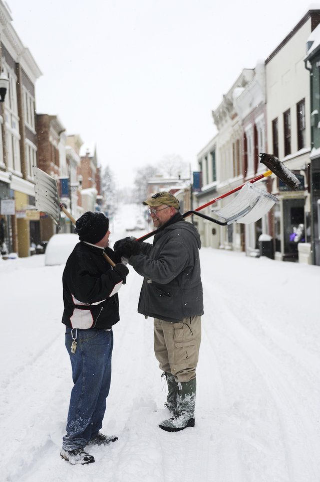 Photo - Ronald Shiflett and Bryan Demory chat in the middle of Beverley before heading out to shovel snow after a snowstorm accumulating over a foot of snow on Thursday, Feb. 13, 2014, in Staunton, Va. (AP Photo/The News Leader, Katie Currid)