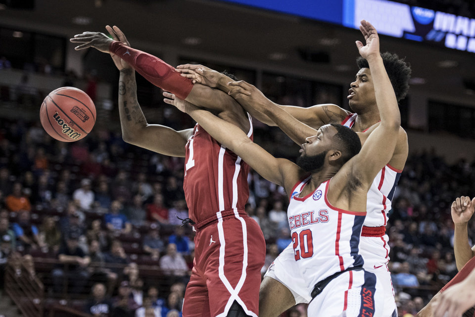 Photo - Mississippi guard D.C. Davis (20) and Bruce Stevens, right, battle for a rebound against Oklahoma forward Kristian Doolittle, left, during a first round men's college basketball game in the NCAA Tournament Friday, March 22, 2019, in Columbia, S.C. (AP Photo/Sean Rayford)