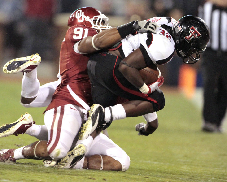 Photo - Oklahoma's R.J. Washington (91) stops Texas Tech's Aaron Crawford (32) during the first half of the college football game between the University of Oklahoma Sooners (OU) and Texas Tech University Red Raiders (TTU) at the Gaylord Family-Memorial Stadium on Saturday, Oct. 22, 2011. in Norman, Okla. Photo by Steve Sisney, The Oklahoman