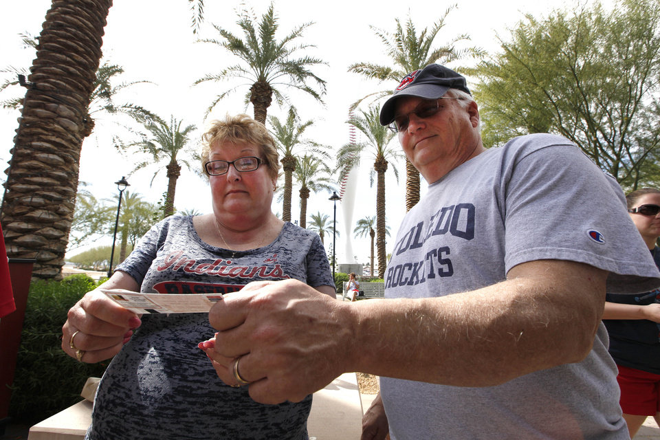 Photo - In this photo taken Wednesday, Feb. 26, 2014, Sue Knieriemen, of Fremont, Ohio, and her brother Charles Bork, of Sylvania, Ohio, check their tickets outside Goodyear Ballpark before an exhibition baseball game between the Cincinnati Reds and the Cleveland Indians in Goodyear, Ariz. After such a long, cold season, Americans across the winter-weary Midwest and the East Coast are desperate to escape to warm-weather destinations in California, Arizona and Florida. (AP Photo/Paul Sancya)