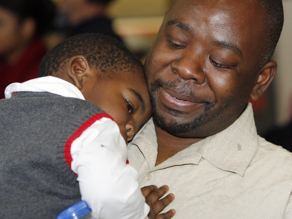 Photo - Humphreys Munai holds his 19-month old son, Austin Munai, after arriving at Will Rogers World Airport in Oklahoma City, Thursday, January 14, 2010. Humphreys Munai was returning from Haiti where he was working for World Neighbors when the recent earthquake devastated the country. Photo by Nate Billings, The Oklahoman