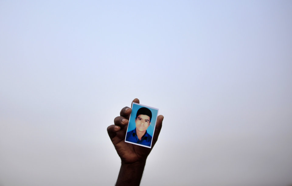 Photo - A man holds up a photograph of his missing relative as they plead for help at the site where the garment factory building collapsed Wednesday in Savar, near Dhaka, Bangladesh, Sunday April 28, 2013. At least 377 people are confirmed to have died in the Wednesday collapse of a shoddily-constructed building this week. The death toll is expected to rise but it is already the deadliest tragedy to hit Bangladesh's garment industry, which is worth $20 billion annually and is the mainstay of the economy.(AP Photo/Wong Maye-E)
