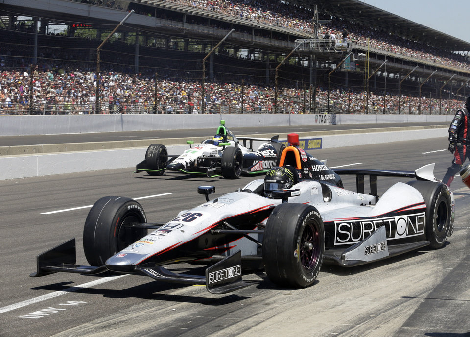 Photo - Kurt Busch pulls out of the pit area under Sebastien Bourdais, of France, during the 98th running of the Indianapolis 500 IndyCar auto race at the Indianapolis Motor Speedway in Indianapolis, Sunday, May 25, 2014. (AP Photo/R Brent Smith)