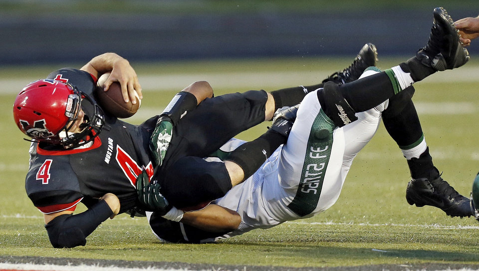 Edmond Santa Fe's Alvin Bazley (41) stops Mustang's Frankie Edwards (4) on a keeper during a high school football game between Mustang and Edmond Santa Fe in Mustang, Okla., Friday, Sept. 28, 2012. Photo by Nate Billings, The Oklahoman