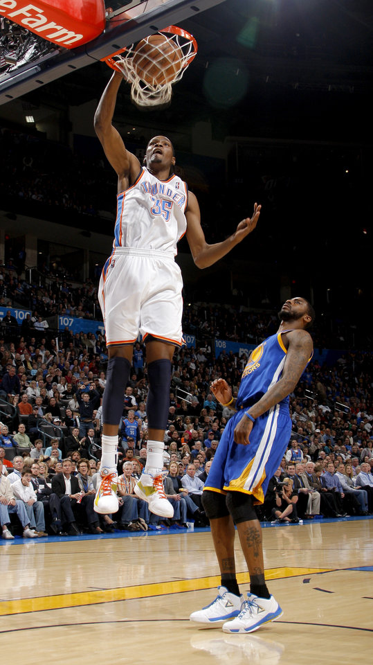 Photo - Oklahoma City's Kevin Durant (35) dunks the ball beside Golden State's Dorell Wright (1) during the NBA basketball game between the Oklahoma City Thunder and the Golden State Warriors at the Oklahoma City Arena, Tuesday, March 29, 2011. Photo by Bryan Terry, The Oklahoman