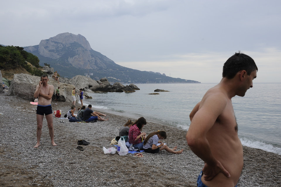 Photo - Russian tourists rest on the Black Sea beach about 35 km. (22 miles) from Yalta, Crimea, Sunday, June 15, 2014. When Russia annexed the Black Sea peninsula of Crimea earlier this year, it regained not only harbors for its navy and abandoned Ukrainian military bases but also long stretches of pebble beaches that were the summer destination of choice for millions of Soviet citizens. The Kremlin is hoping to attract tourists to Crimea, which Russia annexed in March, by asking state-controlled companies to send their employees on free vacation trips.(AP Photo/Andrew Lubimov)