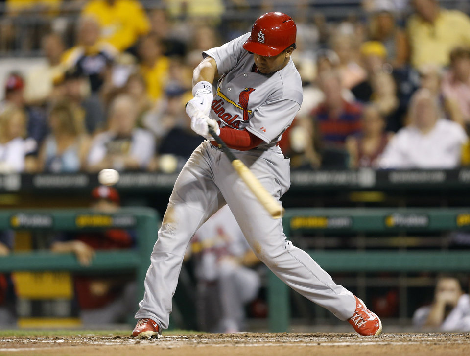 Photo - St. Louis Cardinals' Jon Jay hits a sacrifice fly to drive in Matt Adams with the of the baseball game against the Pittsburgh Pirateson Tuesday, Aug. 26, 2014, in Pittsburgh. (AP Photo/Keith Srakocic)