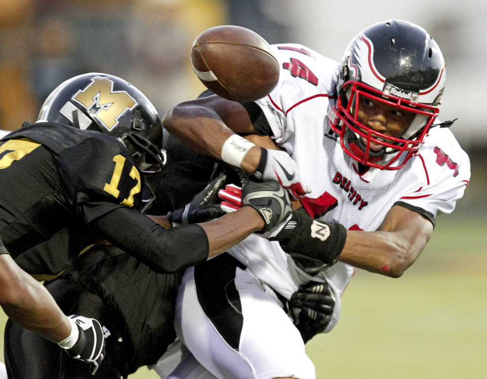 Photo - Del City's Quinn Ashford loses control of the ball as he is hit by Cortrez Colbert of Midwest City during a high school football game in Midwest City, Okla., Friday, September 3, 2010.  Photo by Bryan Terry, The Oklahoman