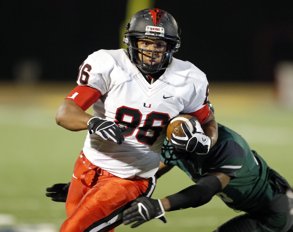 Photo - Union's Chris Hall gets by an Edmond Santa Fe player during the high school football game between Edmond Santa Fe and Union at Wantland Stadium in Edmond, Okla.,  Friday, Nov. 16, 2012. Photo by Sarah Phipps, The Oklahoman