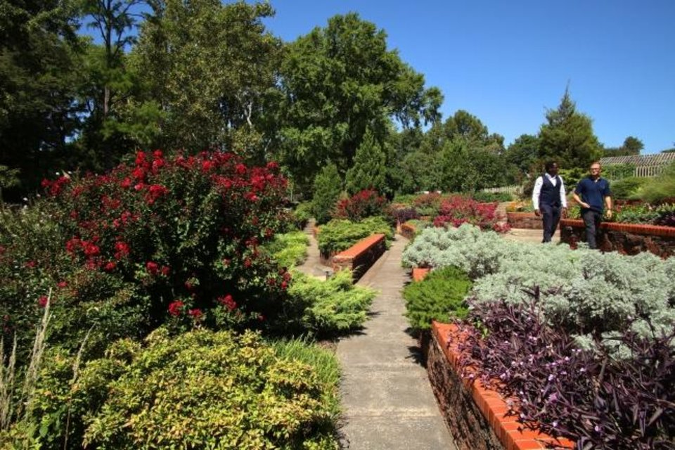 Photo -  Walkers stroll a path at Will Rogers Gardens. [DOUG HOKE/THE OKLAHOMAN]