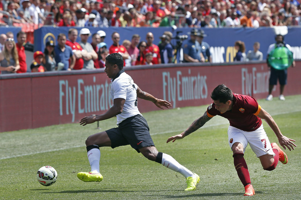 Photo - Manchester United's Antonio Valencia, left, evades coverage by AS Roma's Juan Iturbe during the first half of an exhibition soccer match against  at Mile High Stadium, in Denver, Saturday, July 26, 2014. (AP Photo/Brennan Linsley)