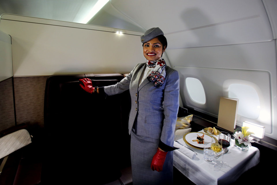 """Photo - An Etihad Airways official poses for a photograph inside the 125-square-foot (11.61-square-meter) area that includes a """"living room"""" partitioned off from the first-class aisle that includes leather seating, chilled minibar and a 32-inch flat-screen TV, at a training facility in Abu Dhabi, United Arab Emirates, Sunday, May 4, 2014. Etihad Airways, a fast-growing Mideast carrier, laid out plans Sunday to offer passengers who find first-class seats a bit too tight a miniature suite featuring a closed-off bedroom, private bathroom and a dedicated butler. (AP Photo/Kamran Jebreili)"""