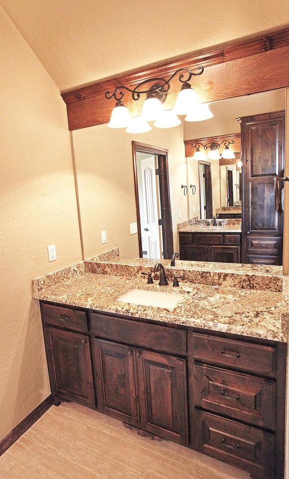 Photo - The master bath of R&R Homes project house has dual vanities, as shown in the reflection of the mirror of this one.  David McDaniel - The Oklahoman