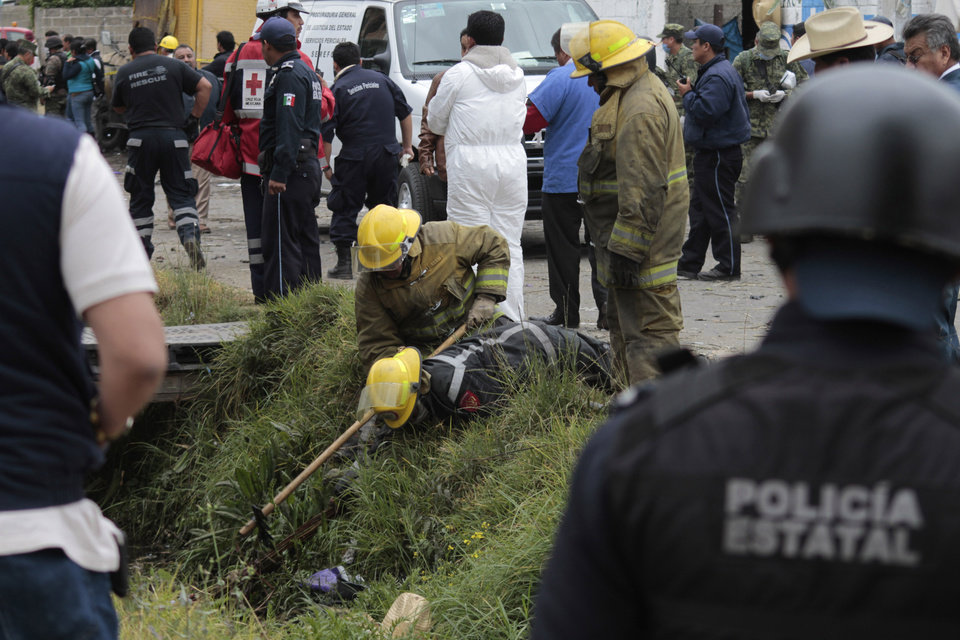 Photo - Emergency workers search for human remains in a ditch after a truck loaded with fireworks exploded during a religious procession in the town of Nativitas, Mexico, Friday, March 15, 2013. A truck loaded with fireworks exploded during a religious procession in this rural village in central Mexico, killing at least nine people and injuring dozens more, authorities said. (AP Photo/J. Guadalupe Perez)