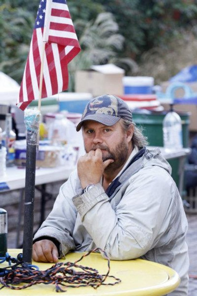 Photo - Occupy OKC protester Justin Myer sits at a table Tuesday in downtown Oklahoma City.
