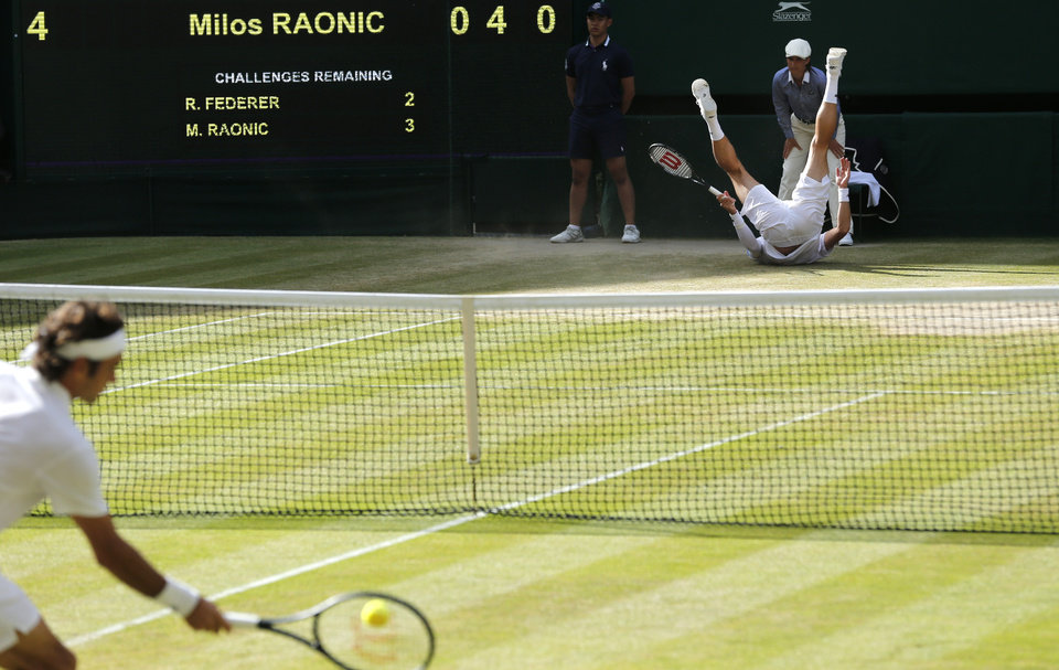 Photo - Milos Raonic of Canada falls over as Roger Federer of Switzerland plays a return during their men's singles semifinal match at the All England Lawn Tennis Championships in Wimbledon, London, Friday, July 4, 2014. (AP Photo/Ben Curtis)