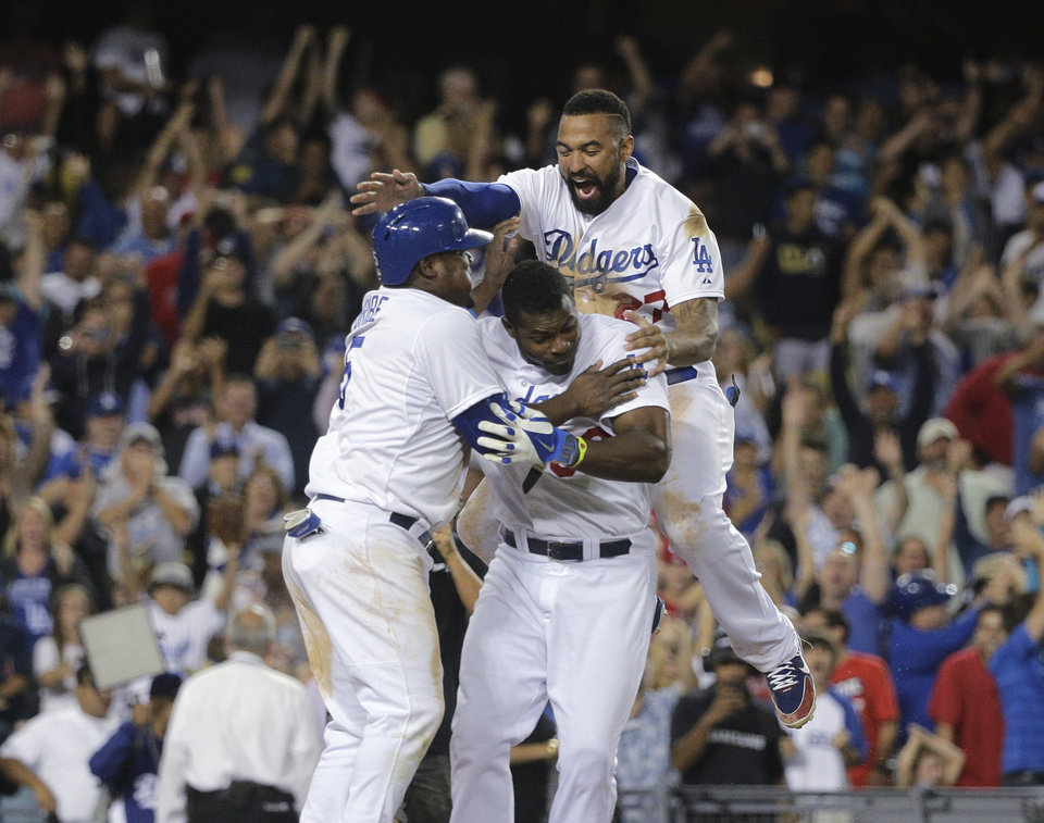 Photo - Los Angeles Dodgers' Juan Uribe, left, Yasiel Puig, center, and Matt Kemp, top, celebrate after Uribe scored the winning run after Andre Ethier's grounder and a throwing error by Los Angeles Angels' David Freese during the ninth inning of a baseball game Tuesday, Aug. 5, 2014, in Los Angeles. The Dodgers won 5-4. (AP Photo/Jae C. Hong)