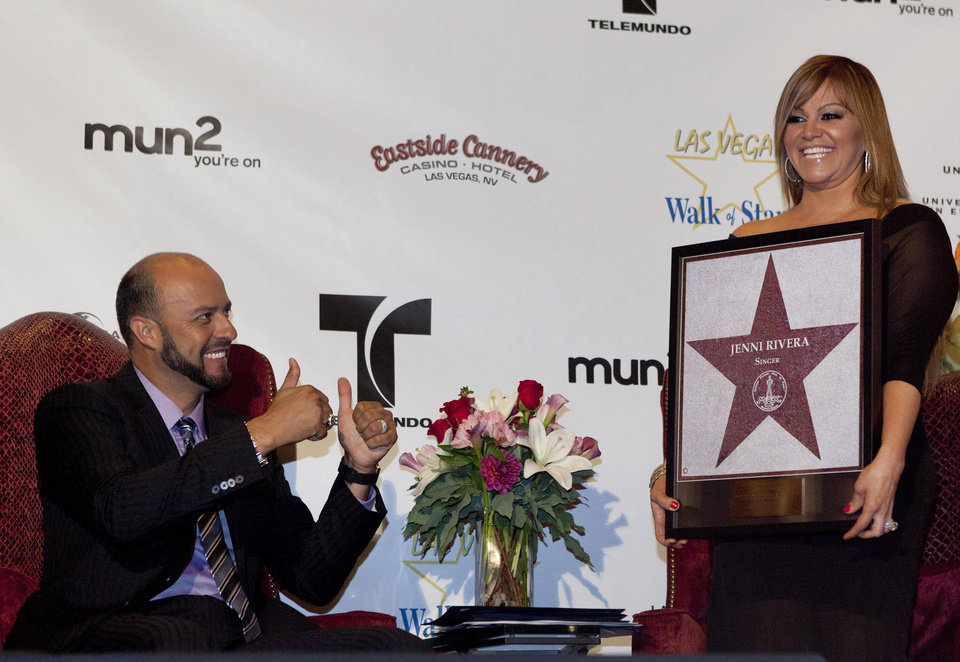 Photo - FILE .- I this July 1, 2011 file photo, singer Jenni Rivera, right, poses with a replica of a star for the Las Vegas Walk of Stars as her husband, former Major League Baseball pitcher Esteban Loaiza, reacts during an official presentation ceremony in Las Vegas. The wreckage of a small plane believed to be carrying Mexican-American music superstar Jenni Rivera was found in northern Mexico on Sunday, Dec. 9, 2012, and there are no apparent survivors, authorities said. (AP Photo/Julie Jacobson, File)