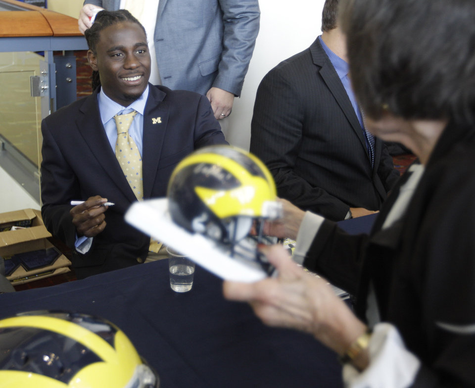 Photo -   Michigan quarterback Denard Robinson signs autographs for fans as part of Big Ten Media Days and Kickoff Luncheon, Friday, July 27, 2012, in Chicago. (AP Photo/M. Spencer Green)