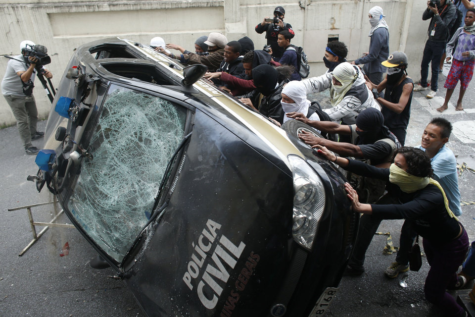 Photo - Demonstrators push over a police car during a protest against the 2014 World Cup in Belo Horizonte, Brazil, Thursday, June, 12, 2014. Demonstrators gathered in downtown Belo Horizonte to protest against the 2014 World Cup soccer tournament. (AP Photo/Victor R. Caivano)