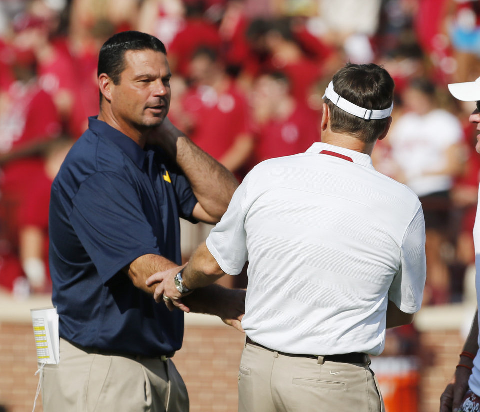 West Virginia special teams coach Joe DeForest shakes hands with Oklahoma head coach Bob Stoops before a college football game between the University of Oklahoma Sooners (OU) and the West Virginia University Mountaineers at Gaylord Family-Oklahoma Memorial Stadium in Norman, Okla., on Saturday, Sept. 7, 2013. Photo by Steve Sisney, The Oklahoman
